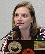 Foto de Bia Barbosa, falando ao microfone e com um notebook à frente