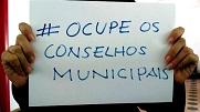 """Duas mãos segurando um cartaz com os dizeres """"Ocupe os Conselhos Municipais"""""""