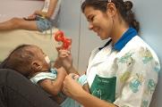Foto de uma profissional de saúde brincando com uma criança