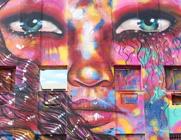 Ilustração remete à arte de rua, com pintura de imagem de um rosto de mulher e com muitas cores