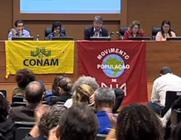 Imagem da mesa de um momento da reunião do CNS na Fiocruz, com a presença de conselheiros e da presidente da Fiocruz, Nísia Trindade