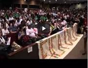 Imagem de trecho do vídeo, com pessoas na plateia, durante a plenária final, no momento de leitura das moções