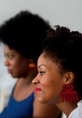 Foto apresenta mulheres negras sentadas uma ao lado da outra, durante Simpósio Internacional de Saúde da População Negra